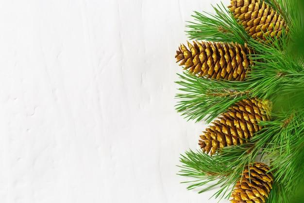 松の枝と天然金の円錐形からのクリスマスの装飾。コピースペース。 Premium写真