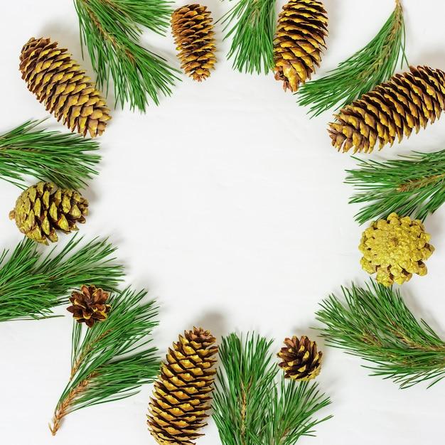コピースペースと明るい背景にクリスマスツリー、ゴールデンコーンの枝からのクリスマスフレーム。 Premium写真