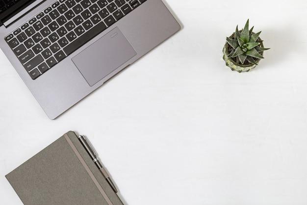 オンライン教育またはビジネスコンセプト。作業スペースフラットレイアウト。ラップトップ、コピーブック、ペン、小さな植物を備えたデスクトップ。上面図。コピースペース。 Premium写真