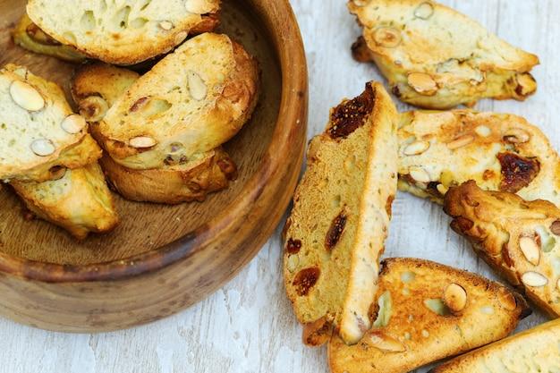 ナッツとイチジクの木製のボウルにイタリアのドライクッキーカンタッチまたはビスコッティ。 Premium写真