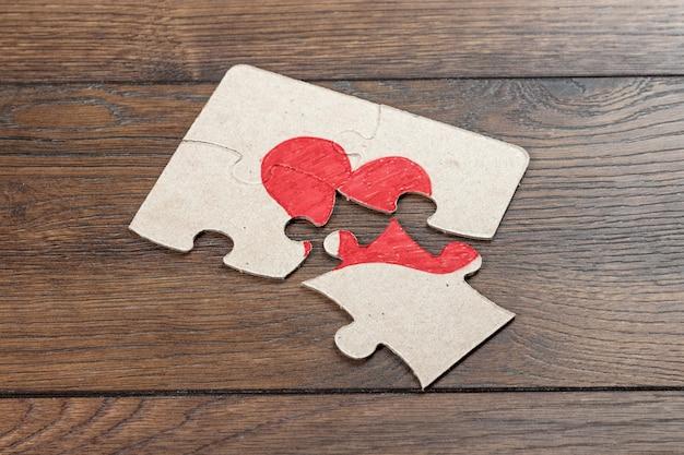 壊れたパズルの部分が心臓を形成します。 Premium写真