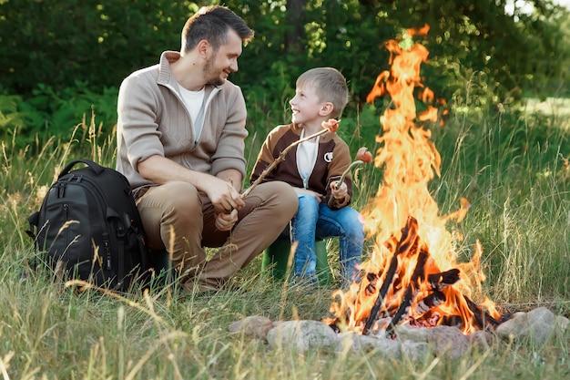 緑の自然の火で父と子。 Premium写真
