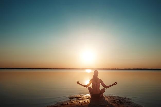 湖と美しい夕日の少女シルエット Premium写真
