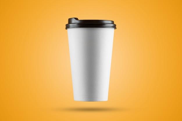 黄色の背景に分離された紙の白いコーヒーカップ Premium写真
