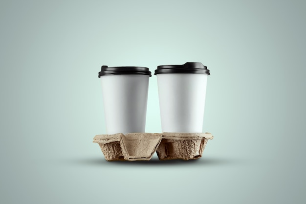 青色の背景に分離された紙の白いコーヒーカップ Premium写真