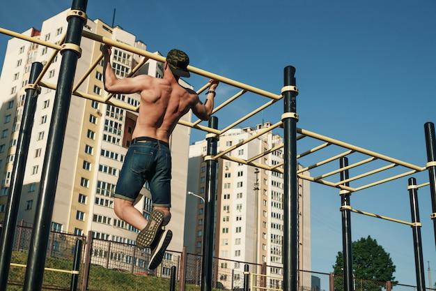 若い男は、スポーツ場、アスリート、都市で屋外トレーニングを自分で引き上げます Premium写真