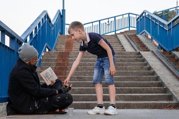 少年は路上でホームレスを助けます。 Premium写真