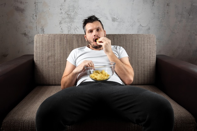 シャツを着た男がソファに横になっていて、チップを食べてスポーツチャンネルを見ています。 Premium写真