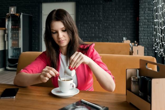 Молодая девушка наливает сливки или молоко в кофе в кафе на деревянный стол Premium Фотографии