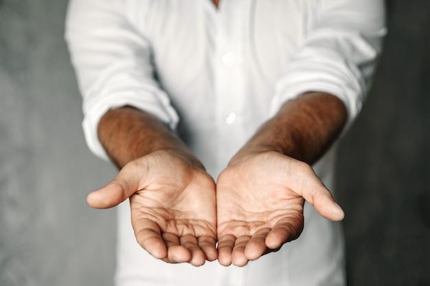 Крупным планом сложенные руки мужчины показывают что-то на белом Premium Фотографии