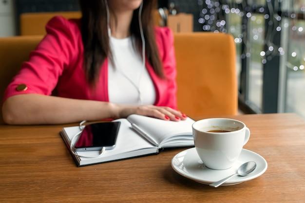 カフェに座って音楽を聴くヘッドフォンの女の子。休憩、ビジネスランチ、日記。 Premium写真