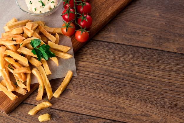 フライドポテト、チェリートマト、木のガーリックソース Premium写真