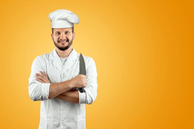 オレンジ色の背景にナイフを持って帽子に笑みを浮かべてシェフ Premium写真