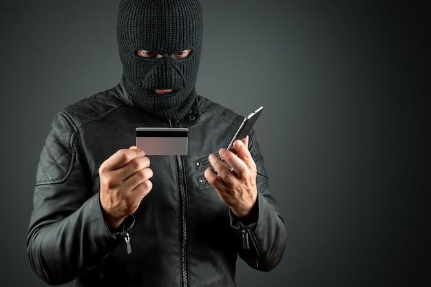 目出し帽の強盗は、暗い背景に彼の手でクレジットカードを保持しています。 Premium写真