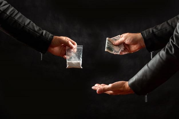 コカインの用量を買うお金を持つ麻薬中毒者の手 Premium写真