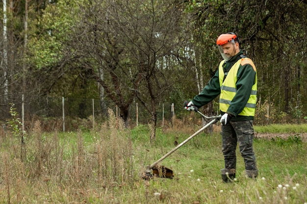 プロの衣装で働く男がトリマーで草を刈る Premium写真