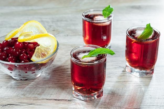 赤い脚付きグラスクランベリーラズベリーレモンとミントとアルコールの冷たいカクテルを撮影 Premium写真