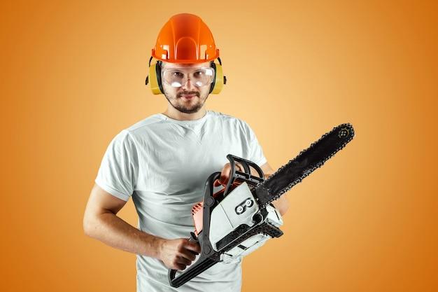 ヘルメットのひげを生やした男はオレンジ色の背景にチェーンソーを保持します。 Premium写真