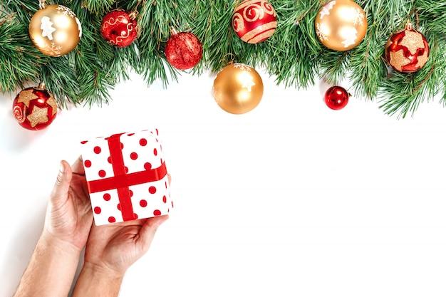モミ、おもちゃ、ギフト、リボン、白で隔離される赤白のボックスを保持している男性の手の枝。分離します。メリークリスマス、そして、あけましておめでとう。 Premium写真