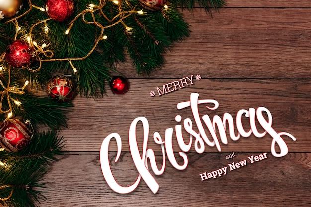 Надпись с рождеством, зеленые ели и измельчения ветвей на деревянном коричневом столе. рождественская открытка, праздник. смешанная техника. Premium Фотографии