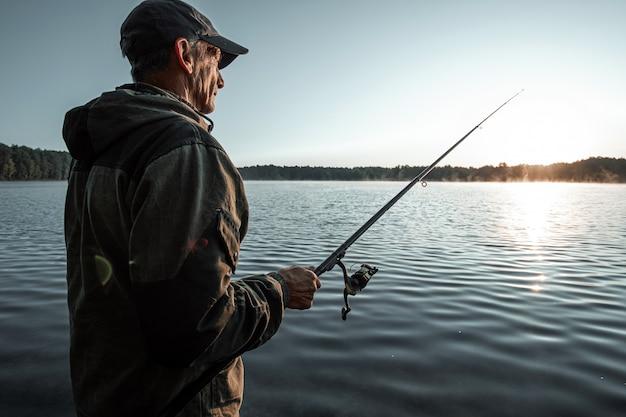 湖の夜明けに男性の漁師が釣り竿をキャッチ Premium写真