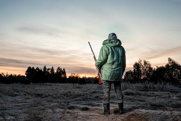 Охотник человек в камуфляже с ружьем во время охоты Premium Фотографии