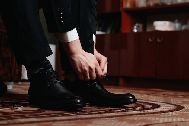 男は黒い靴を結ぶ Premium写真