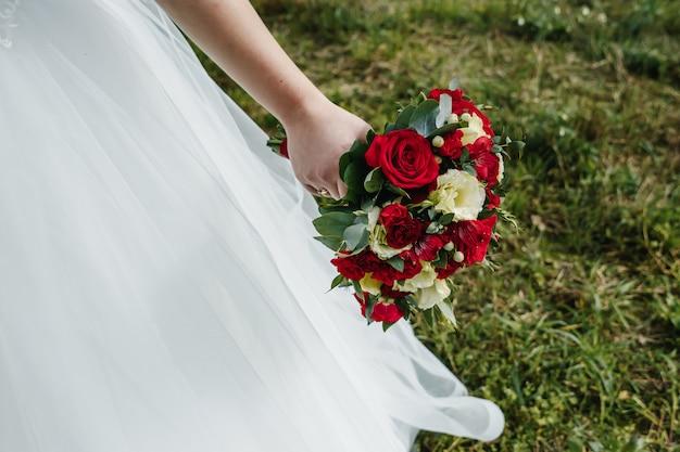 赤と白のバラのウェディングブーケを持って花嫁のクローズアップ。 Premium写真