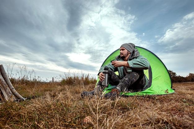 Бородатый мужчина сидит в палатке на фоне природы и озера. путешествия, туризм, кемпинг. Premium Фотографии