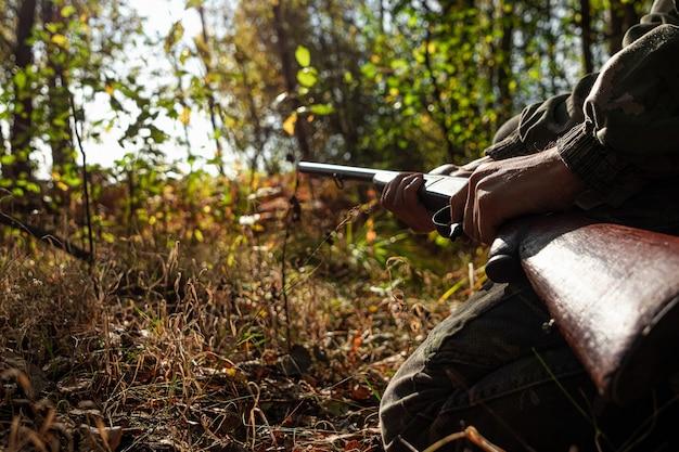 Охотник с ружьем в руках в охотничьей одежде в осеннем лесу Premium Фотографии