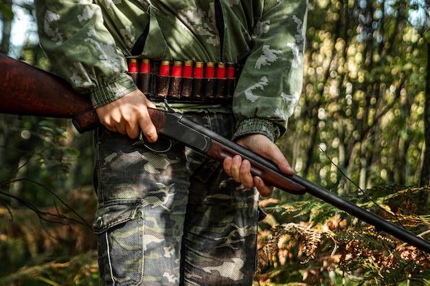 秋の森でハンティング服を着た手に銃を持つハンター Premium写真