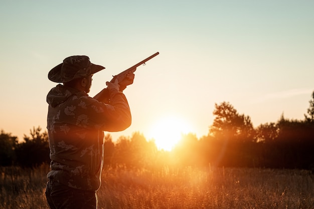 Силуэт охотника в ковбойской шляпе с пистолетом в руках на красивый закат Premium Фотографии