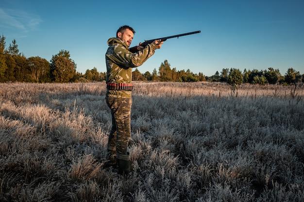 野鳥を探して狩り中に銃でカモフラージュのハンター男 Premium写真