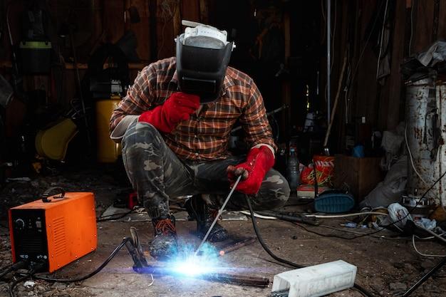 Мужской сварщик в сварочной маске работает с дуговым электродом в своем гараже. сварка, строительство, металлообработка. Premium Фотографии