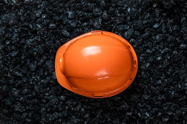 鉱夫のオレンジ色のヘルメットは、石炭の山、露天掘り炭鉱、コピースペースにあります。 Premium写真
