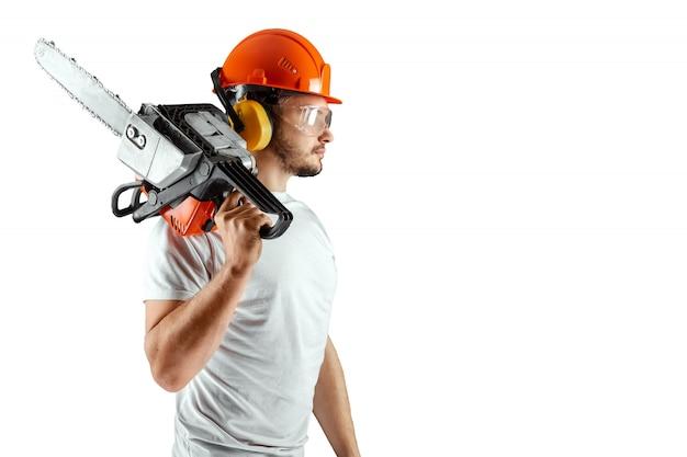 白い背景の上にチェーンソーを握っているヘルメットのひげを生やした男。 Premium写真