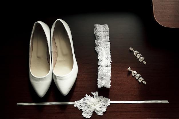 白人女性の結婚式の靴、ガーター、暗い背景の木のイヤリング。 Premium写真