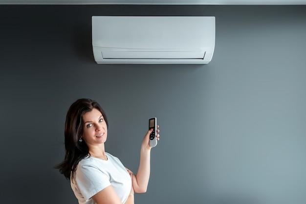 Красивая девушка стоит под кондиционером и потоком свежего холодного воздуха у серой стены. понятие тепла, прохладного воздуха, охлаждения, свежести. Premium Фотографии