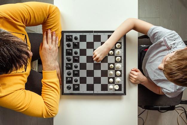 Мальчик с отцом играет в шахматы Premium Фотографии