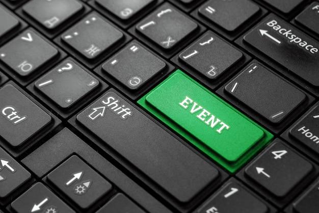 Закройте вверх по зеленой кнопке с событием слова, на черной клавиатуре. творческий фон, копия пространства. концепция волшебной кнопки, события, колонки, информация. Premium Фотографии