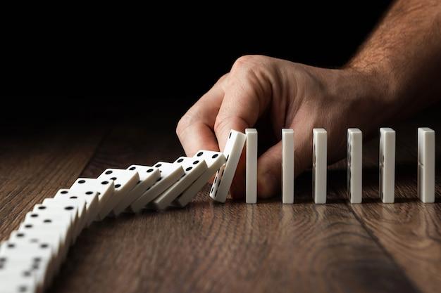 Мужская рука остановила эффект домино Premium Фотографии