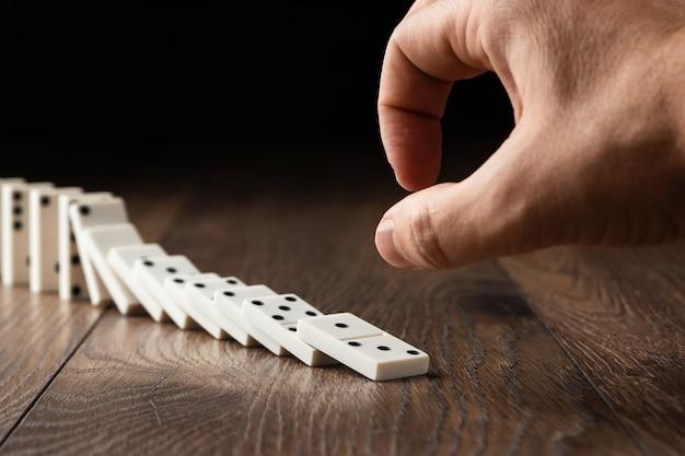 男性の手が白いドミノを押す Premium写真
