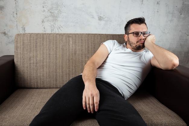 白いシャツを着た男がソファに横になっています。 Premium写真