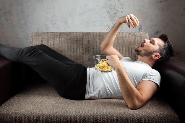 白いシャツを着た男がソファーに横になっていて、チップを食べて、スポーツチャンネルを見ています。 Premium写真