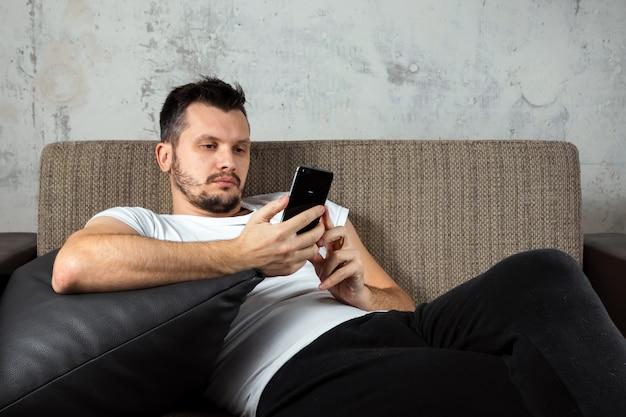 白いシャツを着た男がソファに横になっていると電話に座っています。 Premium写真