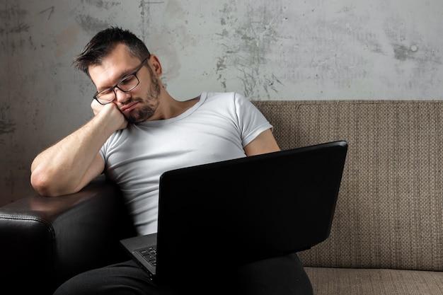 ソファの上に座っている白いシャツを着た男が、ラップトップで仕事で眠りに落ちた。 Premium写真