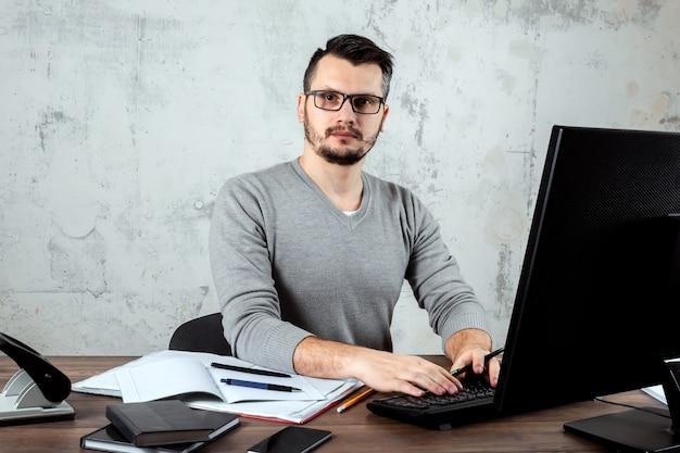 オフィスのテーブルに座っている男の人 Premium写真