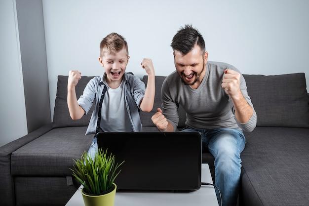 Отец и сын смотрят футбол в ноутбуке дома Premium Фотографии