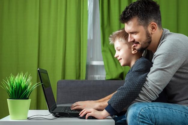 父と息子はラップトップに取り組んでいます。 Premium写真