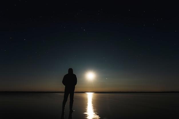 男は星空の下で月の夕日に立っています Premium写真